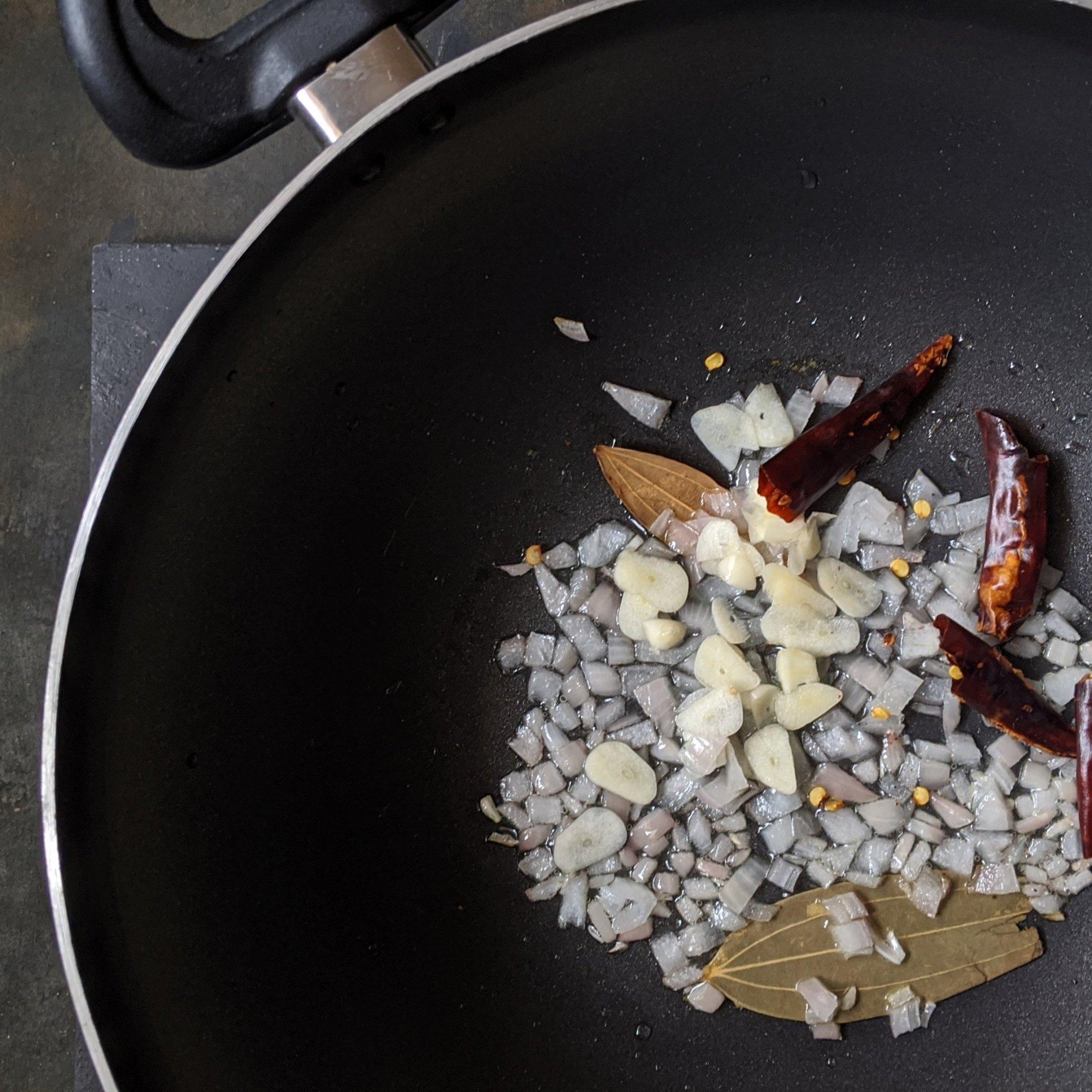 Add garlic, onion, bay leaves and chillis